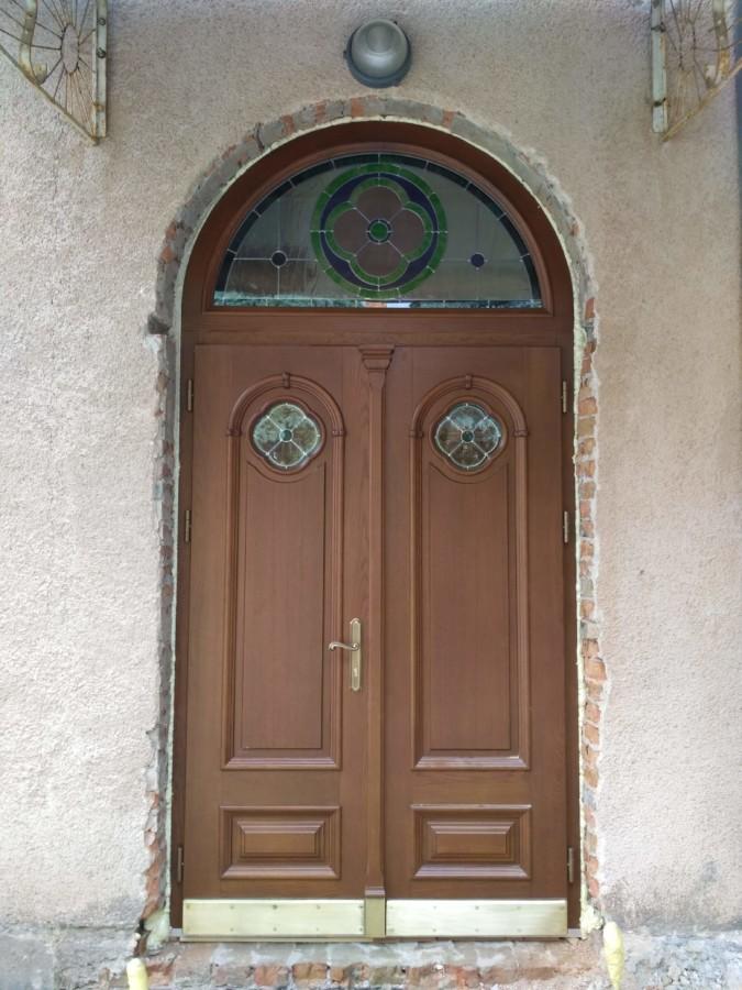 Drzwi wejściowe zdobione blachami mosiężnymi, rzeźbieniami oraz witrażami.